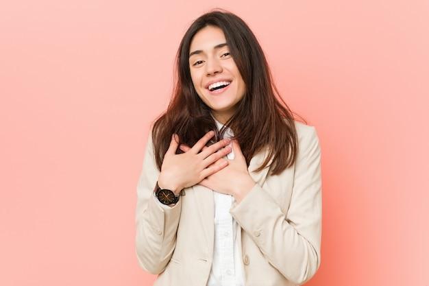 Giovane donna d'affari bruna contro uno sfondo rosa ridendo mantenendo le mani sul cuore