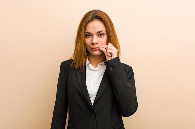 Giovane donna d'affari caucasico con le dita sulle labbra mantenendo un segreto.