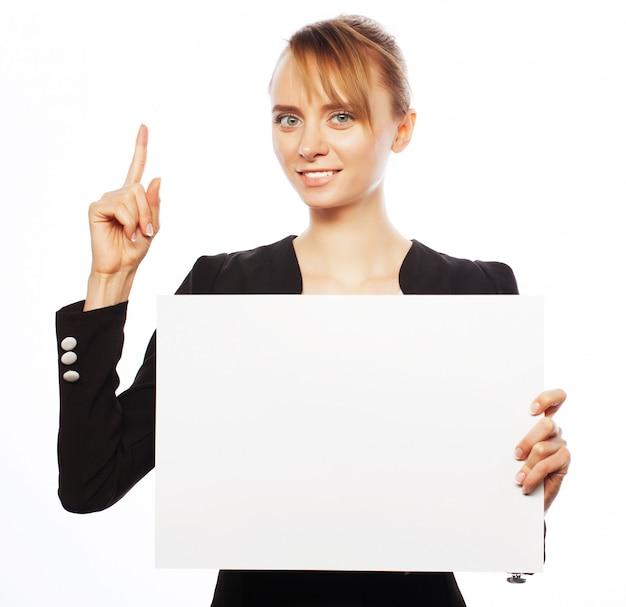 Giovane donna d'affari che mostra cartello bianco