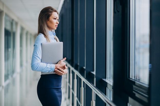 Giovane donna d'affari con il portatile in piedi in un ufficio