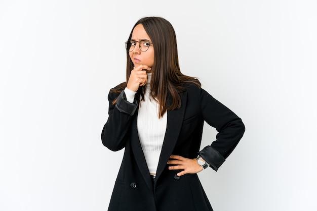 Giovane donna d'affari di razza mista isolata su sfondo bianco contemplando, progettando una strategia, pensando al modo di fare impresa.