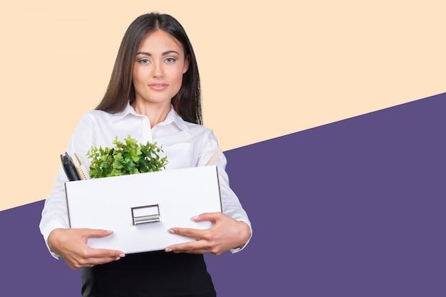 Giovane donna d'affari felice con una scatola per passare a un nuovo ufficio