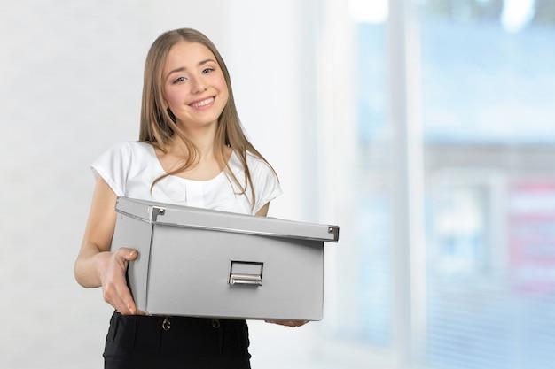 Giovane donna d'affari felice con una scatola per trasferirsi in un nuovo ufficio