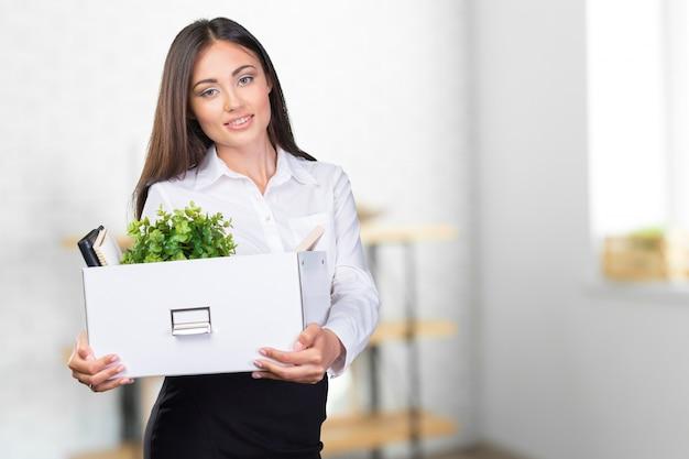 Giovane donna d'affari felice con una scatola per trasferirsi in un nuovo ufficio,