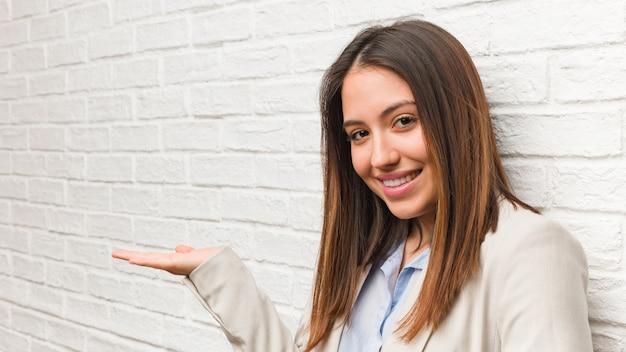 Giovane donna d'affari in possesso di qualcosa con la mano