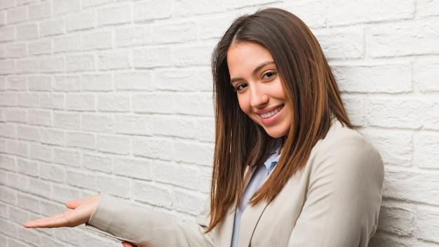 Giovane donna d'affari in possesso di qualcosa con le mani