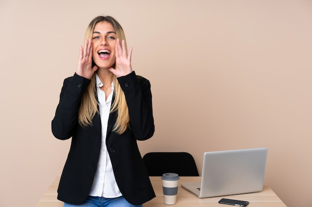 Giovane donna d'affari in un ufficio che grida con la bocca spalancata