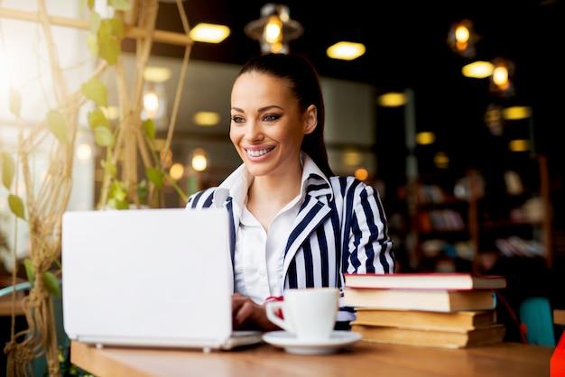 Giovane donna d'affari, lavorando su un computer portatile al bar caffetteria.