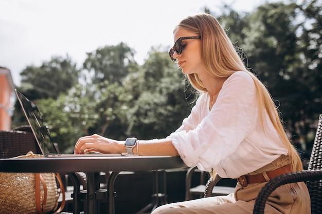 Giovane donna d'affari, lavorando su un computer portatile fuori in un caffè