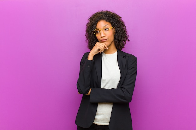 Giovane donna d'affari nera pensando, sentendosi dubbiosa e confusa, con diverse opzioni, chiedendosi quale decisione prendere