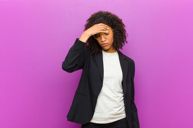 Giovane donna d'affari nera sentirsi stressati, infelici e frustrati, toccando la fronte e soffrendo di emicrania di forte mal di testa