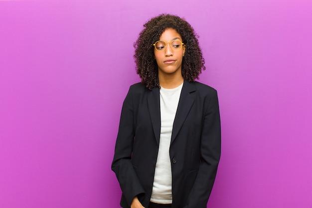 Giovane donna d'affari nero chiedendo, pensando pensieri e idee felici, sognare ad occhi aperti, cercando di copiare lo spazio sul lato