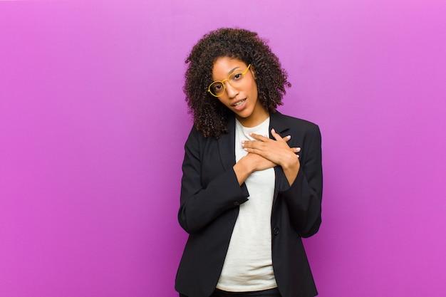 Giovane donna d'affari nero sentirsi romantico felice e innamorato sorridendo allegramente e tenendosi per mano vicino al cuore