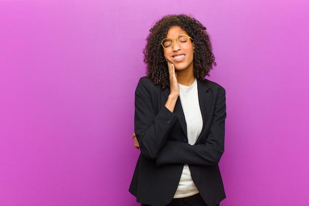 Giovane donna d'affari nero tenendo la guancia e soffre di mal di denti doloroso