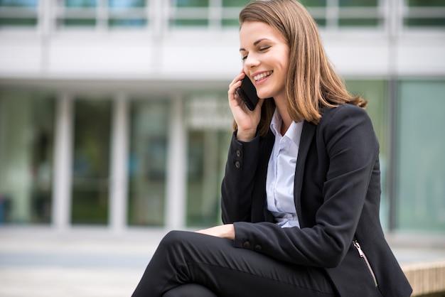 Giovane donna d'affari parlando sul suo cellulare mobile