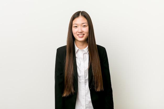 Giovane donna d'affari piuttosto cinese felice, sorridente e allegra.