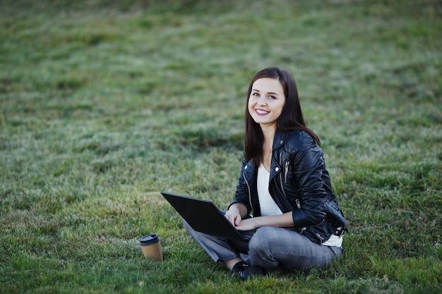 Giovane donna d'affari seduto e lavorando nel parco con il portatile