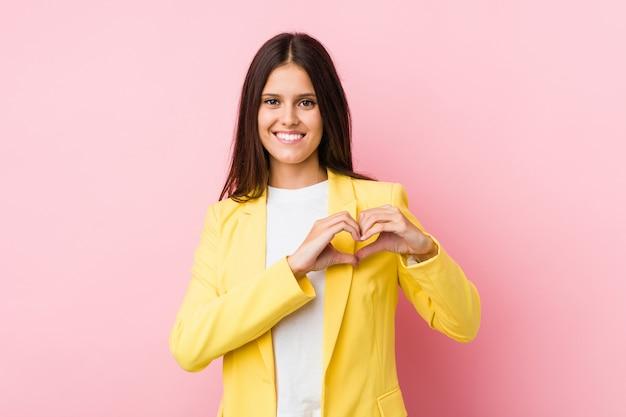 Giovane donna d'affari sorridente e mostrando una forma di cuore con le mani.