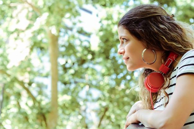 Giovane donna da dietro guardando il parco.