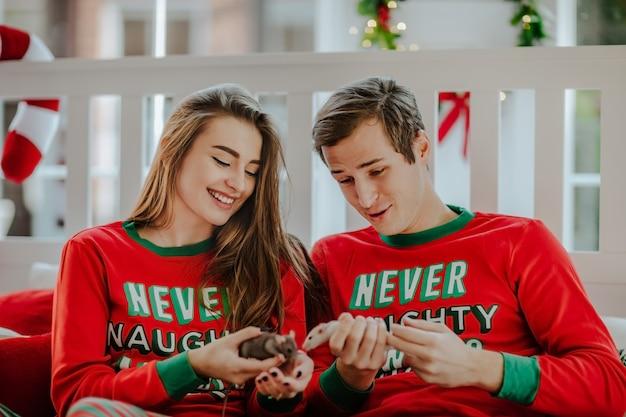 Giovane donna dai capelli abbastanza lunghi e un bell'uomo in pigiama di natale rosso in possesso di due simpatici topi seduti su un letto bianco.