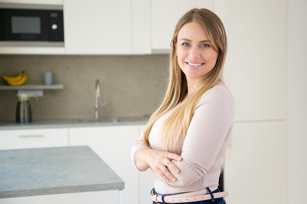 Giovane donna dai capelli bionda attraente allegra in posa con le braccia conserte in cucina