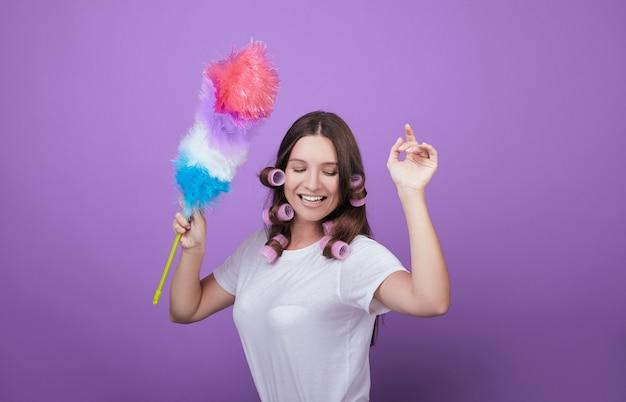 Giovane donna dai capelli castani divertirsi durante la pulizia.