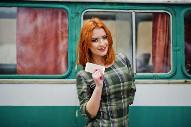 Giovane donna dai capelli rossi donna con cellulare cellulare e cuffie, indossando l'abito a scacchi nel vecchio autobus monovolume vintage.