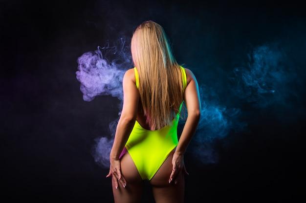 Giovane donna dai capelli scuri in costume da bagno giallo in posa su uno sfondo di fumo viola e blu da uno svapo su uno sfondo nero isolato