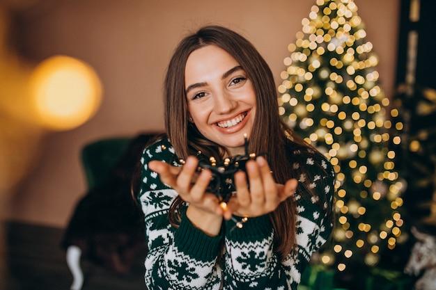Giovane donna dall'albero di natale con le luci d'ardore di natale