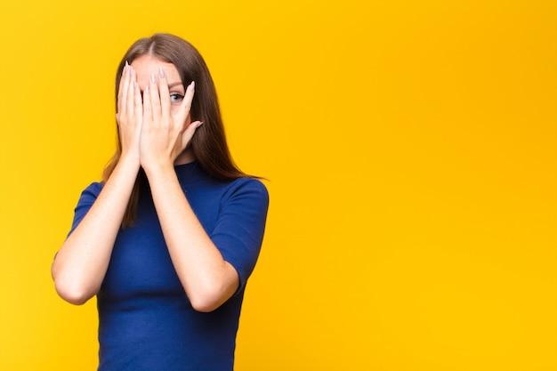 Giovane donna dalla testa rossa che copre il viso con le mani, sbirciando tra le dita con espressione sorpresa e guardando di lato contro la parete piatta