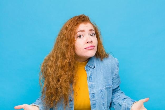 Giovane donna dalla testa rossa che si sente incapace e confusa, non avendo idea, assolutamente perplessa con uno sguardo stupido o sciocco contro la parete blu