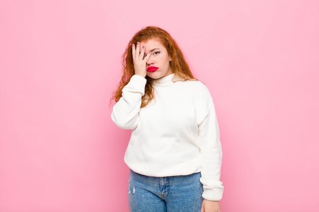 Giovane donna dalla testa rossa sentirsi annoiata, frustrata e assonnata dopo un compito noioso, noioso e noioso, tenendo il viso con la mano sul muro rosa