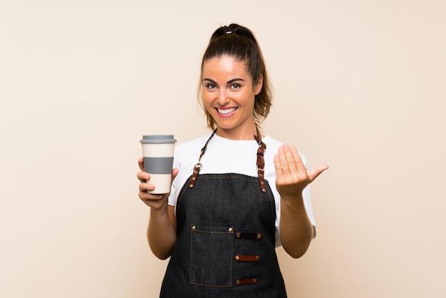 Giovane donna degli impiegati che tiene un caffè asportabile che invita a venire con la mano. felice che tu sia venuto