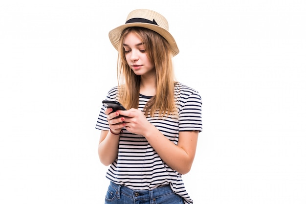 Giovane donna dei pantaloni a vita bassa in cappello di paglia ed occhiali da sole facendo uso del telefono cellulare sopra la parete bianca