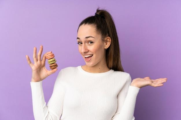 Giovane donna del brunette sopra la parete viola isolata che tiene i macarons francesi variopinti con l'espressione colpita