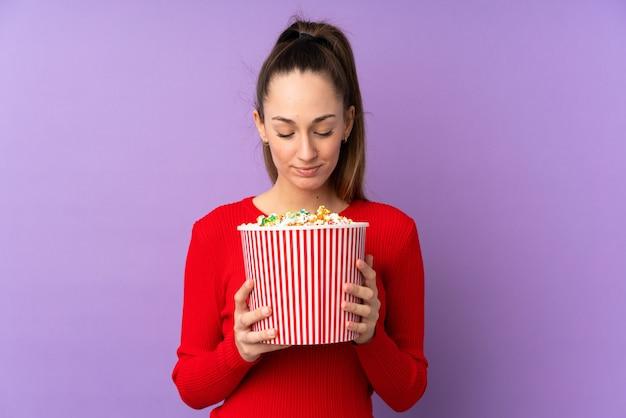 Giovane donna del brunette sopra la parete viola isolata che tiene un grande secchio di popcorn