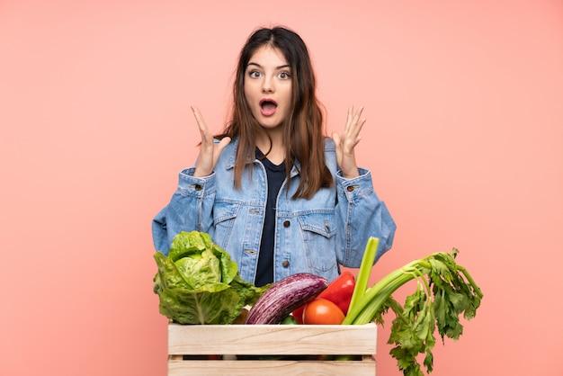 Giovane donna del coltivatore che giudica un canestro pieno degli ortaggi freschi con l'espressione facciale di sorpresa