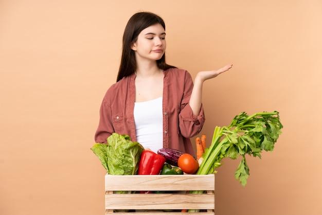 Giovane donna del coltivatore con le verdure di recente selezionate in un copyspace della tenuta della scatola con i dubbi