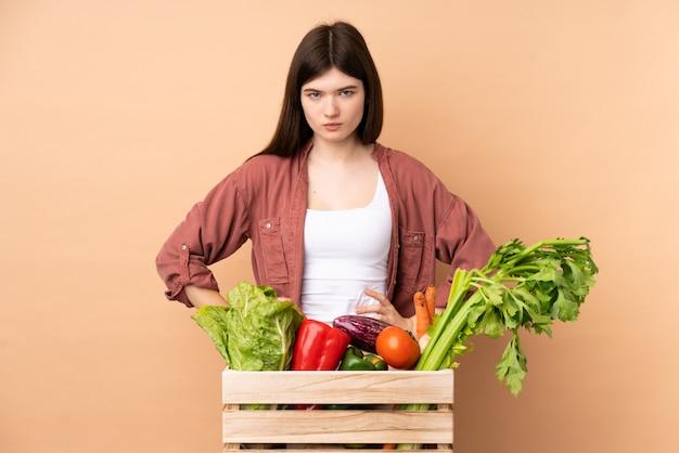 Giovane donna del coltivatore con le verdure di recente selezionate in una scatola arrabbiata
