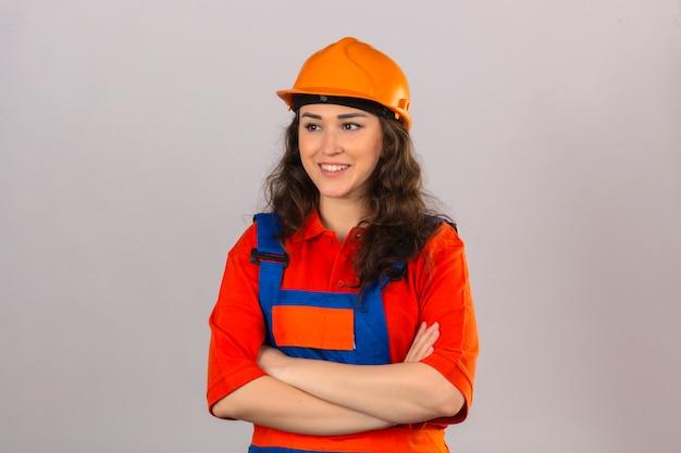 Giovane donna del costruttore in uniforme della costruzione e casco di sicurezza che stanno con la parete bianca isolata amichevole sorridente sopra attraversata armi di armi