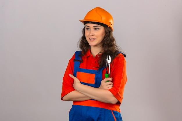 Giovane donna del costruttore in uniforme della costruzione e casco di sicurezza che stanno con le armi attraversate che tengono gli strumenti della costruzione che distolgono lo sguardo con il sorriso sopra la parete bianca isolata