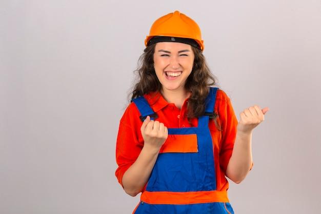 Giovane donna del costruttore in uniforme di costruzione e casco di sicurezza vittoria celebrante felice ed emozionante che esprime grande successo alzando i pugni sopra muro bianco isolato