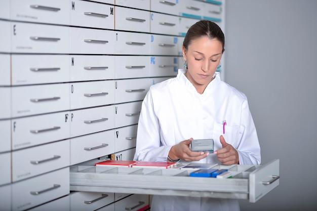 Giovane donna del farmacista che cerca medicina