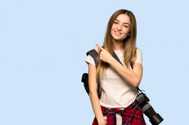 Giovane donna del fotografo che indica il lato per presentare un prodotto sulla parete blu isolata