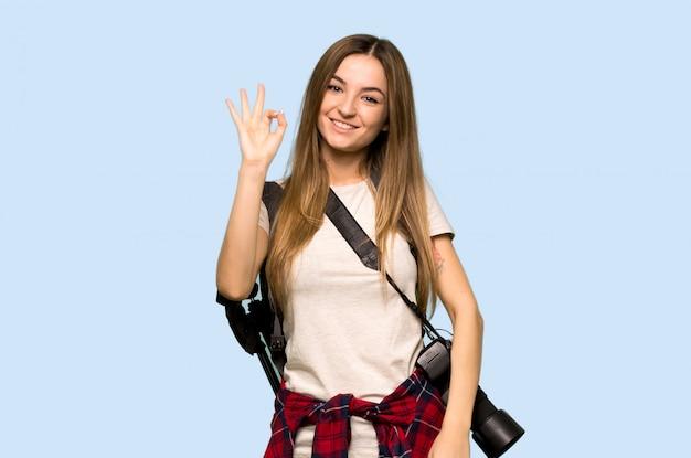 Giovane donna del fotografo che mostra un segno giusto con le dita su fondo blu isolato