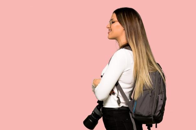 Giovane donna del fotografo nella posizione laterale sulla parete rosa isolata