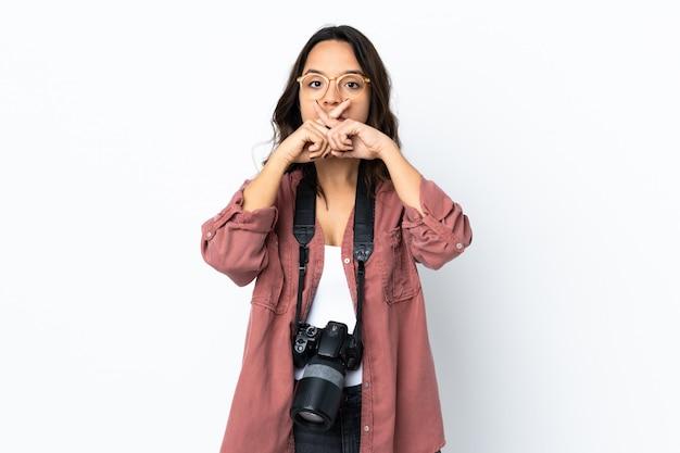 Giovane donna del fotografo sopra la parete bianca che mostra un segno di silenzio gesto