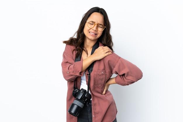 Giovane donna del fotografo sopra la parete bianca isolata che soffre dal dolore alla spalla per aver fatto uno sforzo