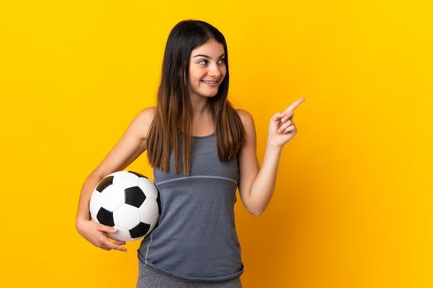 Giovane donna del giocatore di football americano isolata su giallo che indica su una grande idea