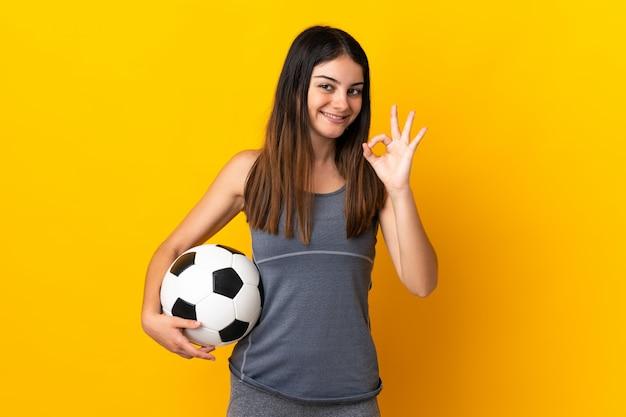 Giovane donna del giocatore di football americano isolata su giallo che mostra segno giusto con le dita